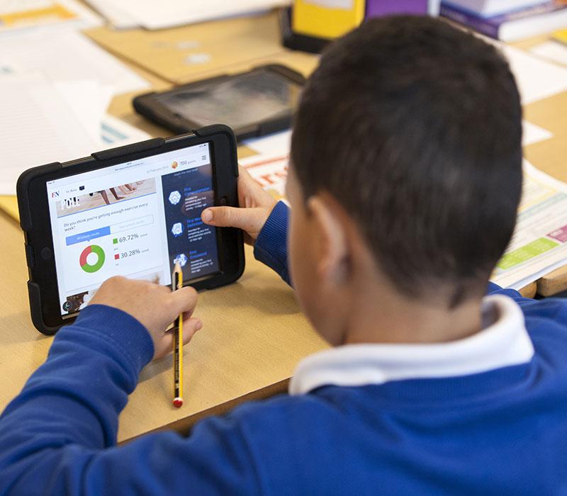 Schoolboy Looking at iHub on Tablet